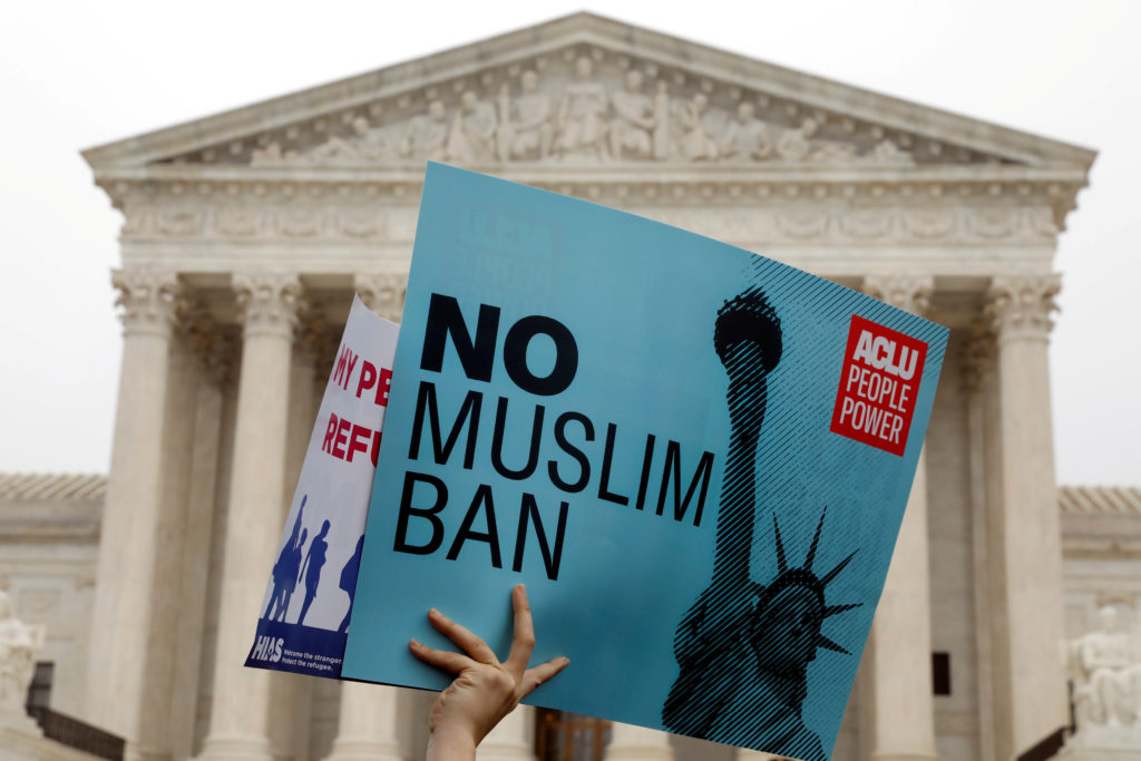 Protesters rally outside the Supreme Court, while the court justices consider case regarding presidential powers as it wei...