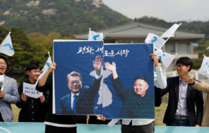 Students hold posters of South Korea's President Moon Jae-in and North Korea's leader Kim Jong Un during a pro-unification rally on April 26 ahead of the upcoming summit between North and South Korea. Photo by Jorge Silva/Reuters