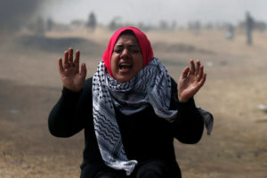 A woman demonstrator reacts to tear gas fired by Israeli troops during clashes at a protest at the Israel-Gaza border where Palestinians demand the right to return to their homeland, east of Gaza City April 20, 2018. REUTERS/Mohammed Salem