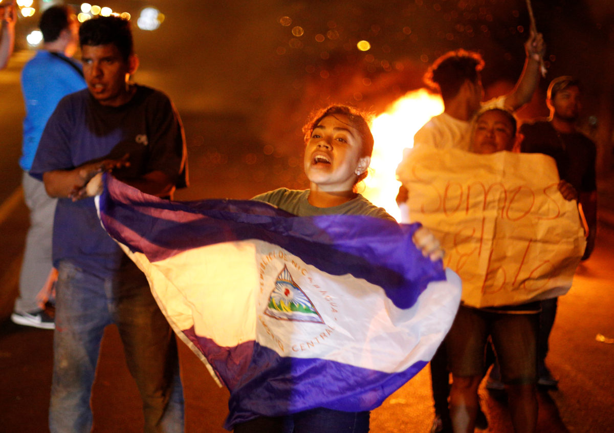 A demonstrator holds up a Nicaragua flag next to a burning barricade as demonstrators take part in a protest over a controversial reform to the pension plans of the Nicaraguan Social Security Institute (INSS) in Managua, Nicaragua April 21, 2018. REUTERS/Jorge Cabrera