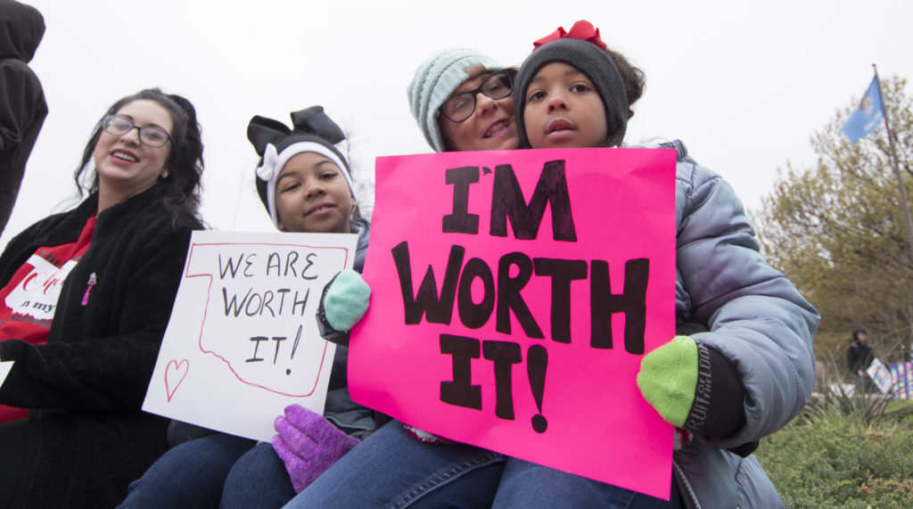 OKLAHOMA CITY, OK - APRIL 2: Natalie Armstrong (left) and her two daughters Payton and Payzlyn, along with her mother Katrina Sinor rally at the state capitol on April 2, 2018 in Oklahoma City, Oklahoma. Thousands of teachers and supporters are scheduled to rally Monday at the state Capitol calling for higher wages and better school funding. Armstrong said she has spent $3,000 this year for school supplies Teachers are walking off the job after a $6,100 pay raise was rushed through the Legislature and signed into law by Gov. Mary Fallin. (Photo by J Pat Carter/Getty Images)