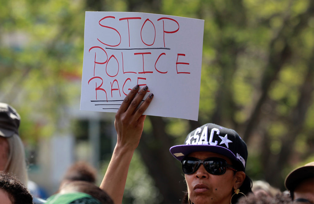 A demonstrator holds a sign at a rally to protest the police shooting of Stephon Clark, in Sacramento, California, U.S., March 31, 2018. REUTERS/Bob Strong - RC1F62230E20