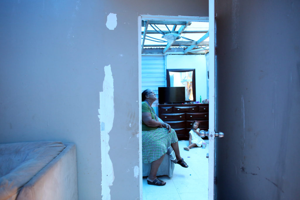 Milagros Nolazco sits in her bedroom and near her granddaughter Isya, as a plastic sheet replaces the roof hit by Hurrican...
