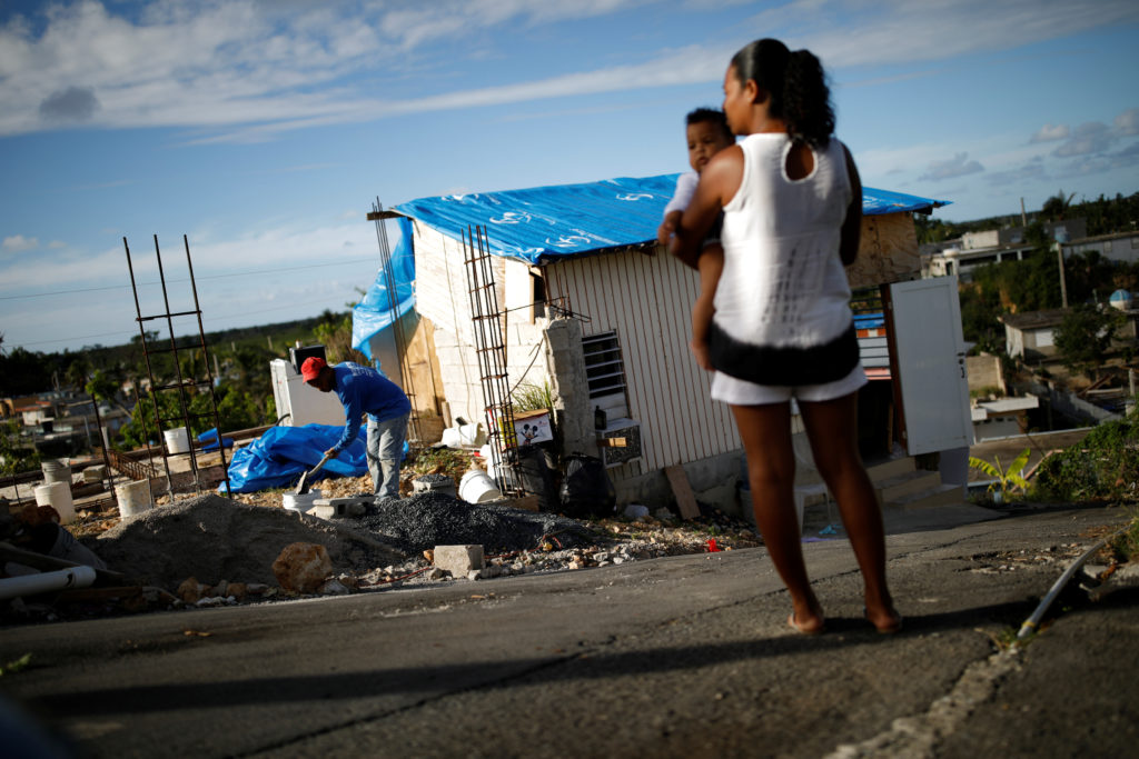 Samuel Vasquez rebuilds his house, which was partially destroyed by Hurricane Maria, while his wife Ysamar Figueroa looks on, whilst carrying their son Saniel, at the squatter community of Villa Hugo in Canovanas, Puerto Rico, December 11, 2017. Villa Hugo is a settlement initially formed by people whose houses were damaged or destroyed by Hurricane Hugo in 1989. REUTERS/Carlos Garcia Rawlins