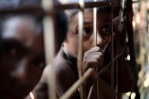 Rohingya refugee child looks through the fence at a refugee camp in Cox's Bazar, Bangladesh March 22, 2018. REUTERS/Mohammad Ponir Hossain