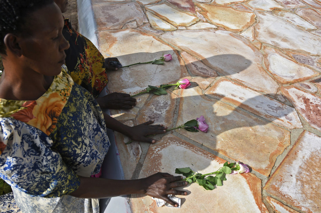Rwandese refugees lay flowers at Kasensero genocide memorial site in Rakai district on April 21, 2018 during the 24th commemoration of the 1994 genocide against the Tutsi in Rwanda. - 2827 bodies of Rwandese citizens were found on River Kagera in Uganda and buried at this site.