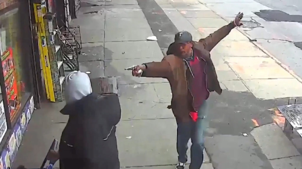 Saheed Vassell points a metal pipe at a pedestrian in Brooklyn April 4, 2018, in a still image from surveillance video released by the New York Police Department in New York City, New York, U.S. on April 5, 2018. NYPD/Handout via REUTERS.