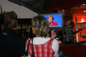 Germans watch Chancellor Angela Merkel on an outdoor television in September 2009. Photo by Larisa Epatko/PBS NewsHour