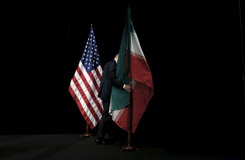 "A staff member removes the Iranian flag from the stage after a group picture with foreign ministers and representatives of Unites States, Iran, China, Russia, Britain, Germany, France and the European Union during the Iran nuclear talks at the Vienna International Center in Vienna, Austria July 14, 2015. Iran and six major world powers reached a nuclear deal on Tuesday, capping more than a decade of on-off negotiations with an agreement that could potentially transform the Middle East, and which Israel called an ""historic surrender"". REUTERS/Carlos Barria"