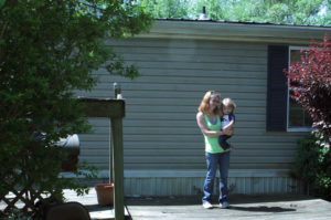 Casey Britton holds her younger son, Gavin, on the front porch of their home in Linden, Tennessee. Photo by Laura Santhanam/PBS NewsHour