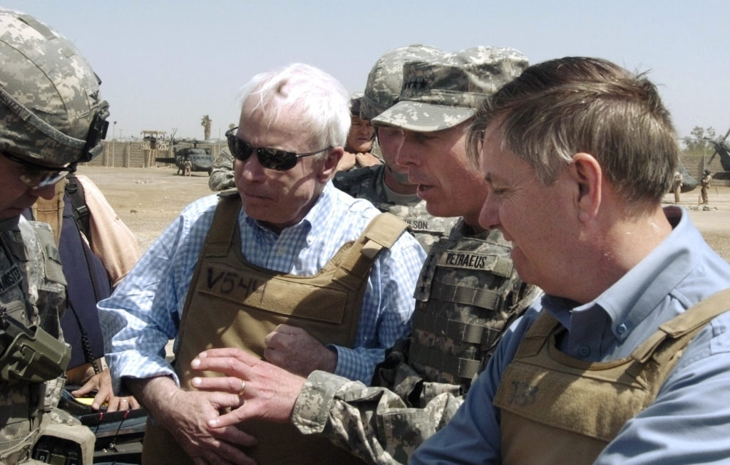 U.S. Senators John McCain (R-AZ) and Lindsey Graham (R-SC) (R) get a briefing from General David Petraeus (2nd R), U.S. Commander in Iraq, and an unidentified military escort (L) as they visit the Shorga marketplace and interacted with local merchants while walking the streets of Baghdad April 1, 2007. Photo taken April 1, 2007. REUTERS/Sergeant Matthew Roe/10th Public Affairs Operations Center/Handout  (IRAQ).  EDITORIAL USE ONLY. NOT FOR SALE FOR MARKETING OR ADVERTISING CAMPAIGNS. - GM1DUYLXNSAA