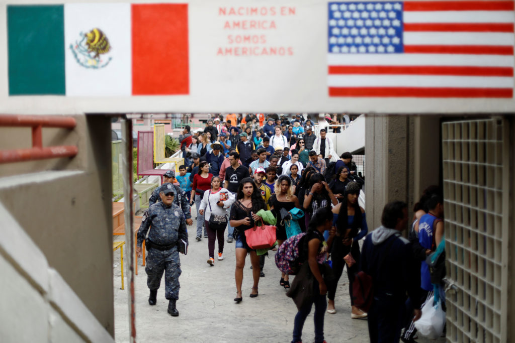In April, members of a caravan of migrants from Central America walk towards the U.S. border and customs facility, where t...