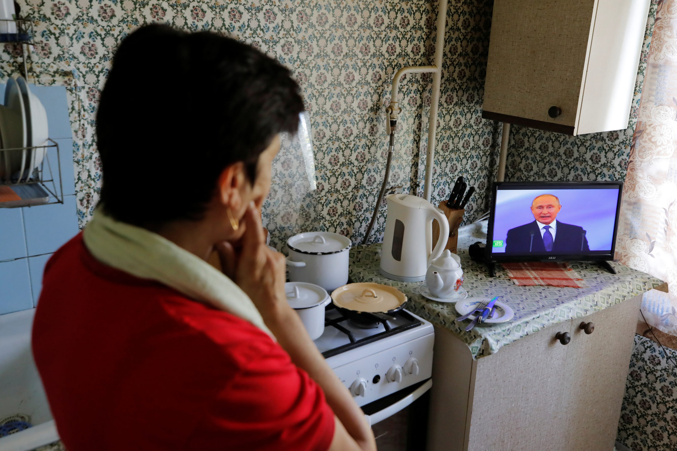 A woman watches a ceremony to inaugurate Vladimir Putin as President of Russia while cooking a meal inside an apartment in Moscow, Russia. Photo by Maxim Shemetov/Reuters