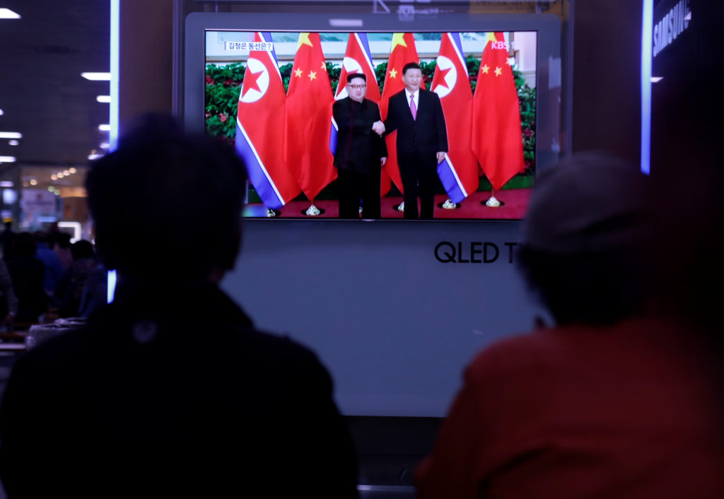 People watch a TV news report about the meeting between North Korean leader Kim Jong Un and Chinese President Xi Jinping a...