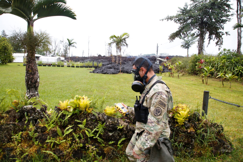 Lieutenant Aaron Hew Lew, of the Hawaii National Guard, measures levels of toxic sulfur dioxide gas in the Leilani Estates subdivision during ongoing eruptions of the Kilauea Volcano, Hawaii, U.S., May 8, 2018. REUTERS/Terray Sylvester - RC1828CC2000
