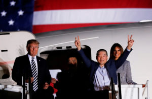 One of the Americans formerly held hostage in North Korea gestures next to President Donald Trump and first lady Melania Trump, upon their arrival at Joint Base Andrews, Maryland. Photo by Jonathan Ernst/Reuters