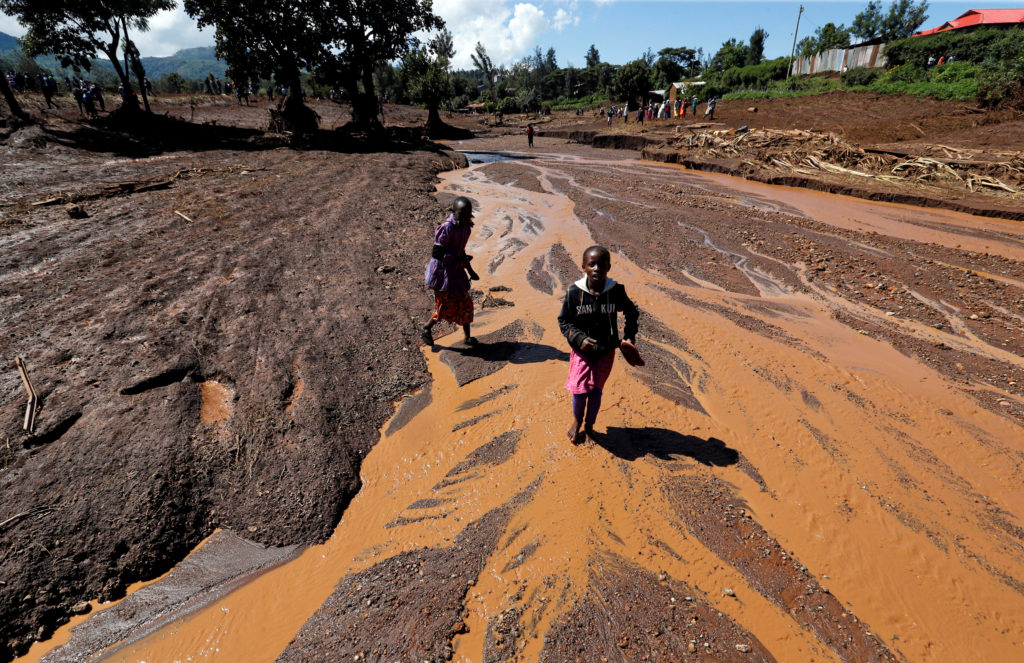 Children walk in muddy waters after a dam burst, which unleashed water at nearby homes, in Solio, a town near Nakuru, Keny...