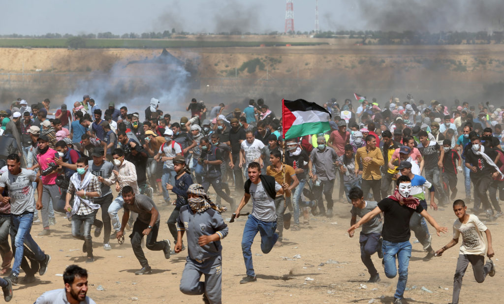 Palestinian demonstrators run from tear gas fired by Israeli forces during a protest demanding the right to return to their homeland, at the Israel-Gaza border in the southern Gaza Strip on May 11. Photo by Ibraheem Abu Mustafa/Reuters