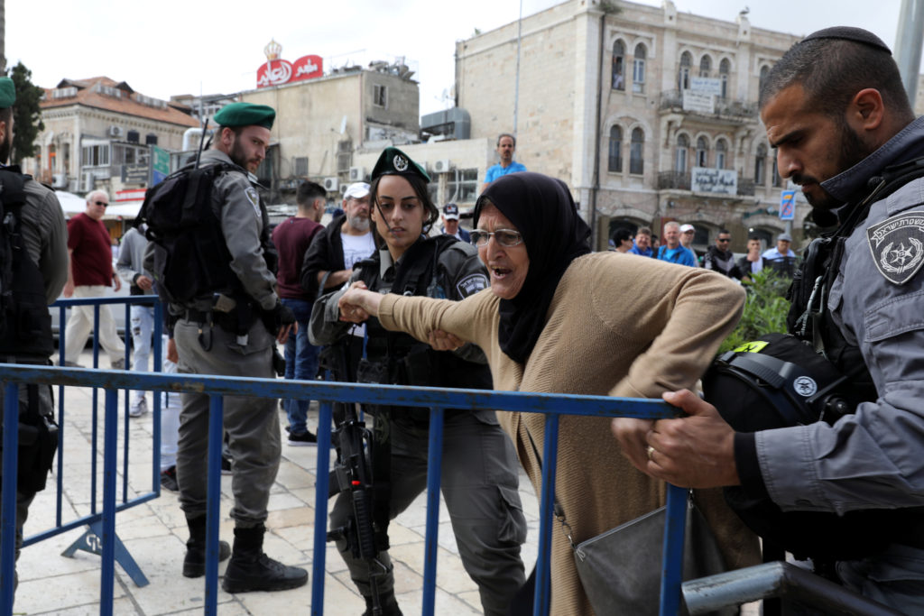 Israeli security forces personnel scuffle with a Palestinian woman outside Jerusalem's Old City's Damascus Gate, May 13, 2018. Photo by Ammar Awad/Reuters