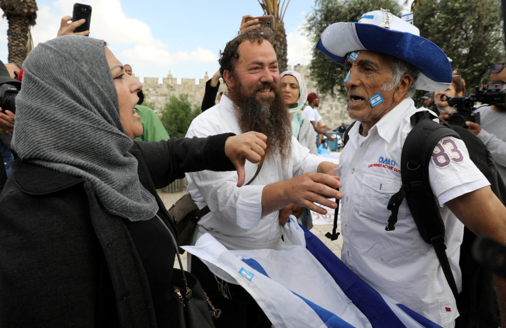An Israeli man holds an Israeli flag as he argues with a Palestinian woman ahead of the annual Jerusalem Day parade outside Jerusalem's Old City's Damascus Gate