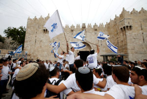 Israelis celebrate as they hold Israeli flags during a parade marking the annual Jerusalem Day, at Damascus Gate in Jerusalem's Old City