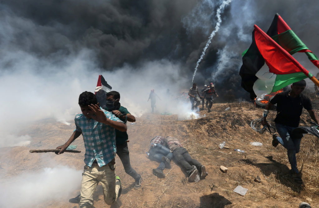 Palestinian demonstrators run for cover during a protest at the Israel-Gaza border in the southern Gaza Strip on May 14. Photo by Ibraheem Abu Mustafa/Reuters