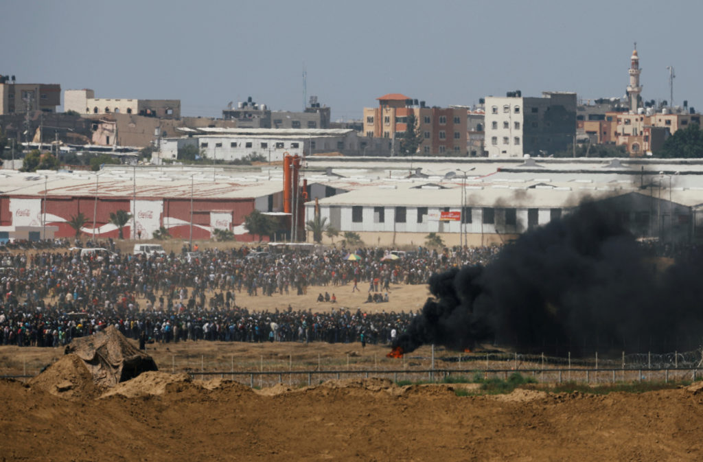 Smoke rises in front of Palestinians who protest against U.S. embassy move to Jerusalem and ahead of the 70th anniversary of Nakba, at the Israel-Gaza border. Photo by Amir Cohen/Reuters