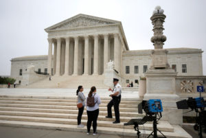 A police officer speaks with tourists before a decision was released allowing the legalization of sports betting at the Supreme Court in Washington, U.S., May 14, 2018. REUTERS/Joshua Roberts - RC15186577E0