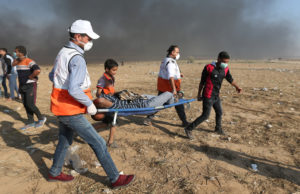A wounded Palestinian demonstrator is evacuated after inhaling tear gas fired by Israeli troops during a protest in the southern Gaza Strip on May 15. Photo by Ibraheem Abu Mustafa/Reuters