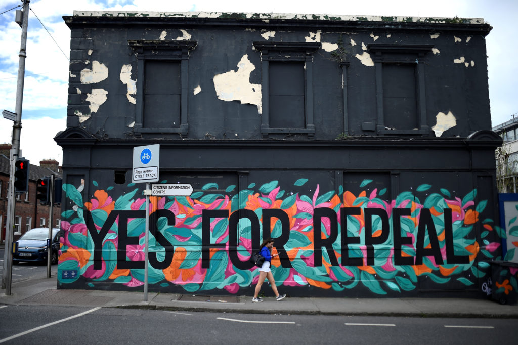 A woman walks past a pro-choice mural on the side of a building ahead of a 25th May referendum on abortion law in Dun Laoghaire Ireland