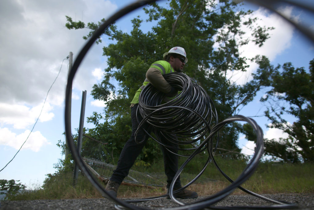 A contractor of the U.S. Army Corps of Engineers carries cables as …