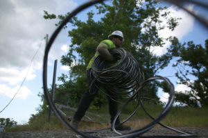 A contractor of the U.S. Army Corps of Engineers carries cables as the island's fragile power system is still reeling from the devastation wrought by Hurricane Maria eight months ago, in Utuado, Puerto Rico May 17, 2018. Photo by Alvin Baez/Reuters