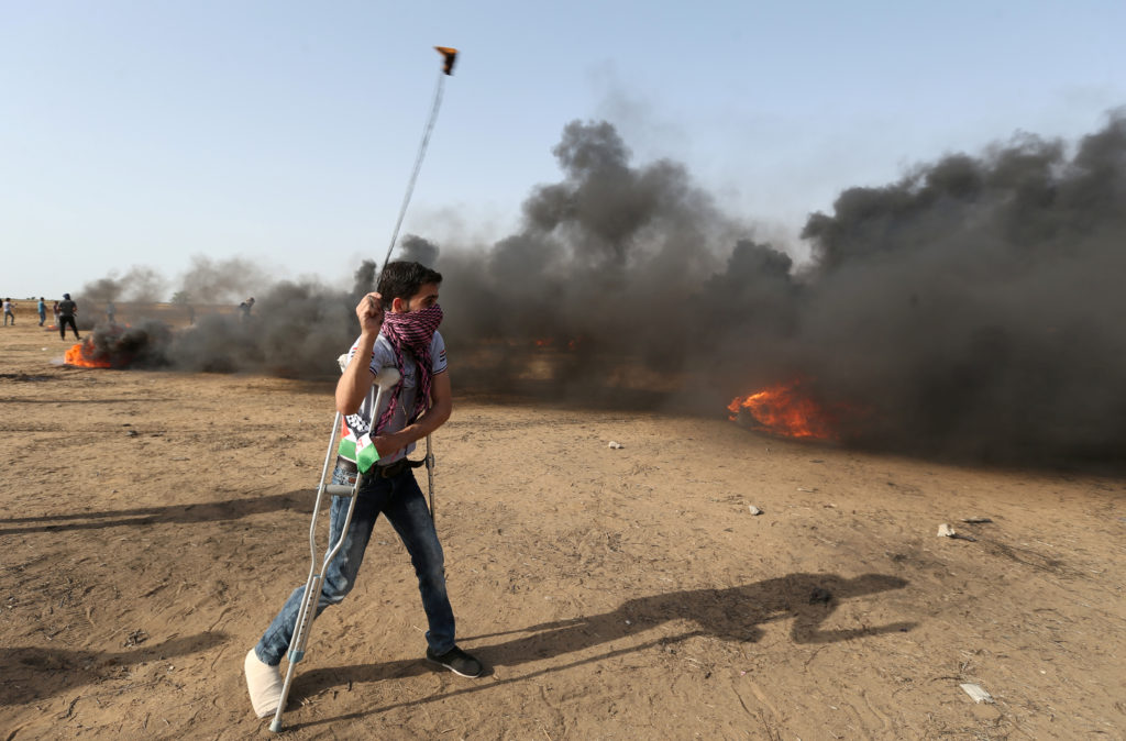 A demonstrator with crutches uses a sling during a protest where Palestinians demand the right to return to their homeland, at the Israel-Gaza border, in the southern Gaza Strip. Photo by Ibraheem Abu Mustafa/Reuters