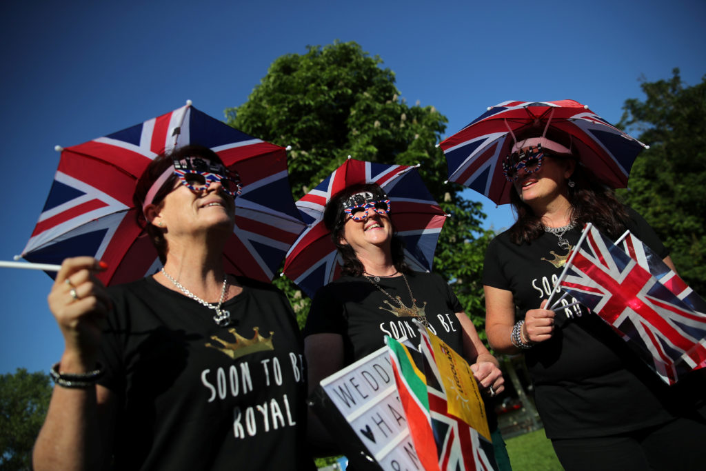 Royals fans with Union Jack umbrella hats partake in the celebration. Photo by Marko Djurica/Reuters