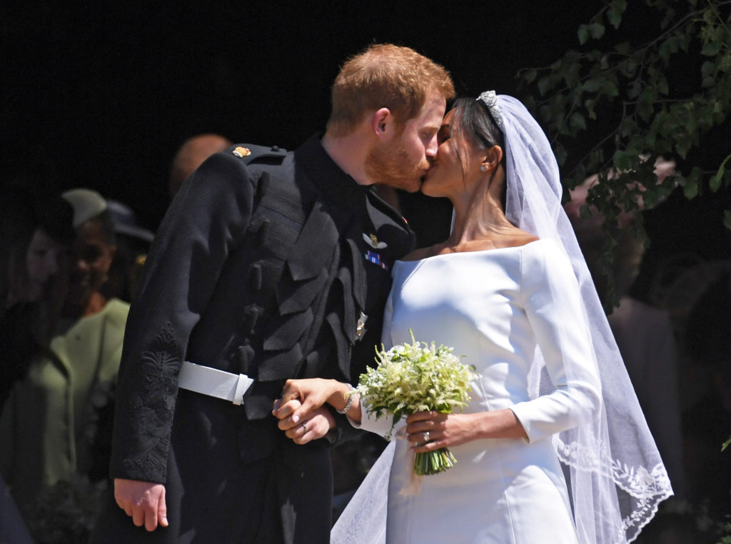 Britain's Prince Harry kisses Meghan Markle as they leave St. George's Chapel in Windsor Castle on May 19. Photo by Neil H...