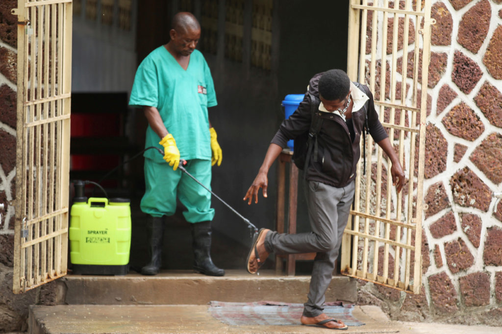 A health worker sprays a visitor with chlorine after leaving the isolation facility, prepared to receive suspected Ebola cases, at the Mbandaka General Hospital in the Democratic Republic of Congo on May 20. Photo by Kenny Katombe/Reuters