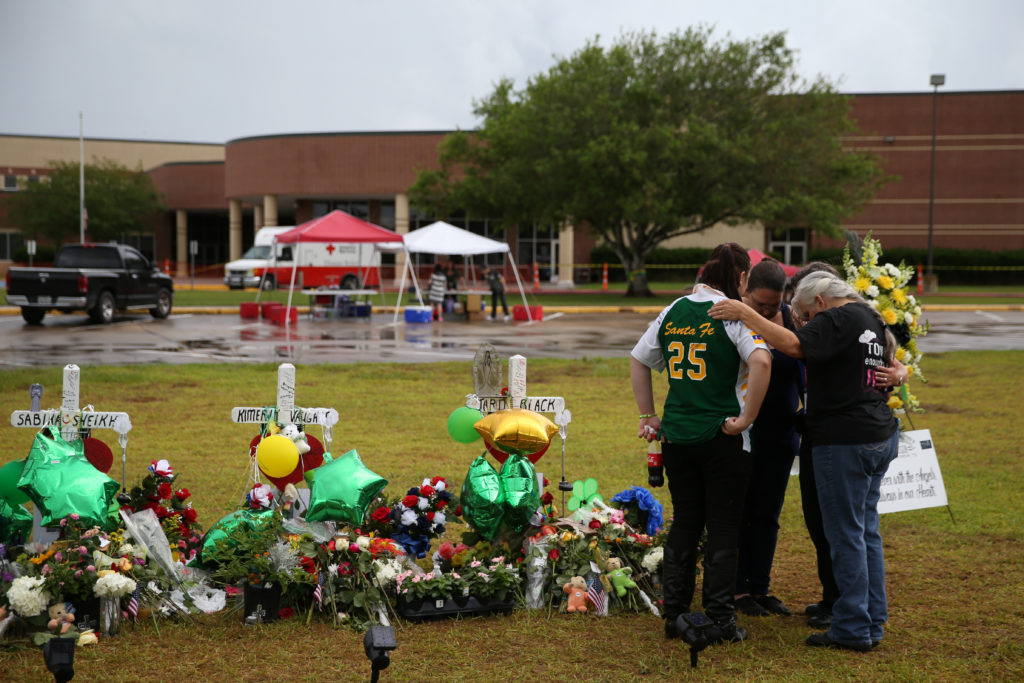 People mourn at a makeshift memorial left in memory of the victims killed in a shooting at Santa Fe High School in Santa Fe, Texas. Photo by Loren Elliott/Reuters