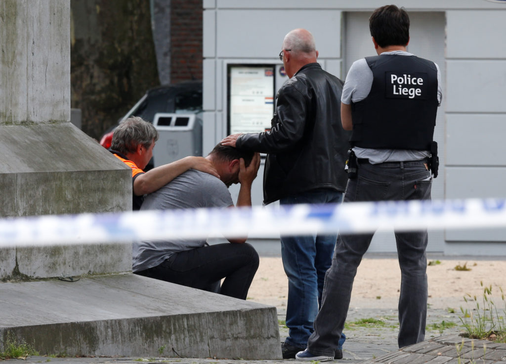 A man is consoled at the scene of a shooting in Liege, Belgium. Photo by Francois Lenoir/Reuters