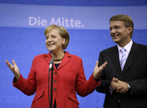 Angela Merkel, German chancellor and leader of the conservative Christian Democratic Union party, and party general secretary Ronald Pofalla (right) greet supporters after the first exit polls in the German general election at party headquarters in Berlin on Sept. 27, 2009. Photo by Kai Pfaffenbach/Reuters