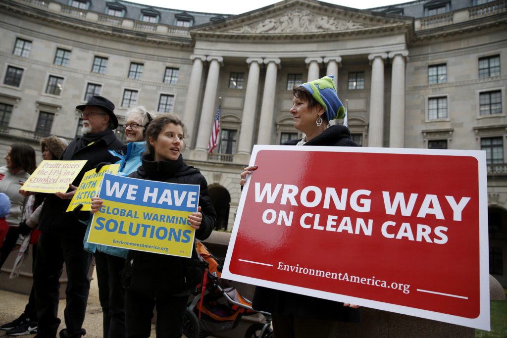 A group of protesters rally against the announcement to reduce automobile emission standards by Administrator of the Environmental Protection Agency (EPA) Scott Pruitt in front of the EPA building in Washington, U.S., April 3, 2018. REUTERS/Joshua Roberts