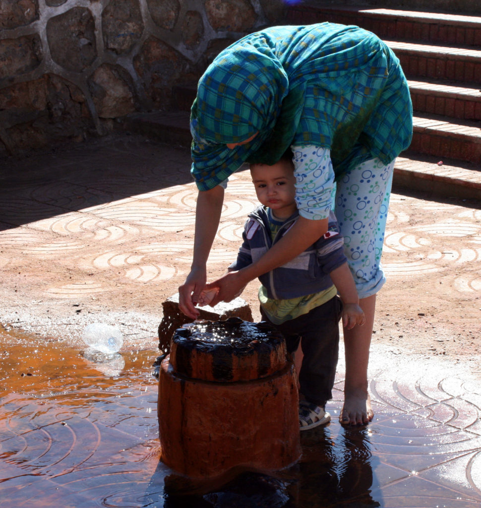 A woman washes her son's hands in a fountain in Laayoune. Photo by Larisa Epatko