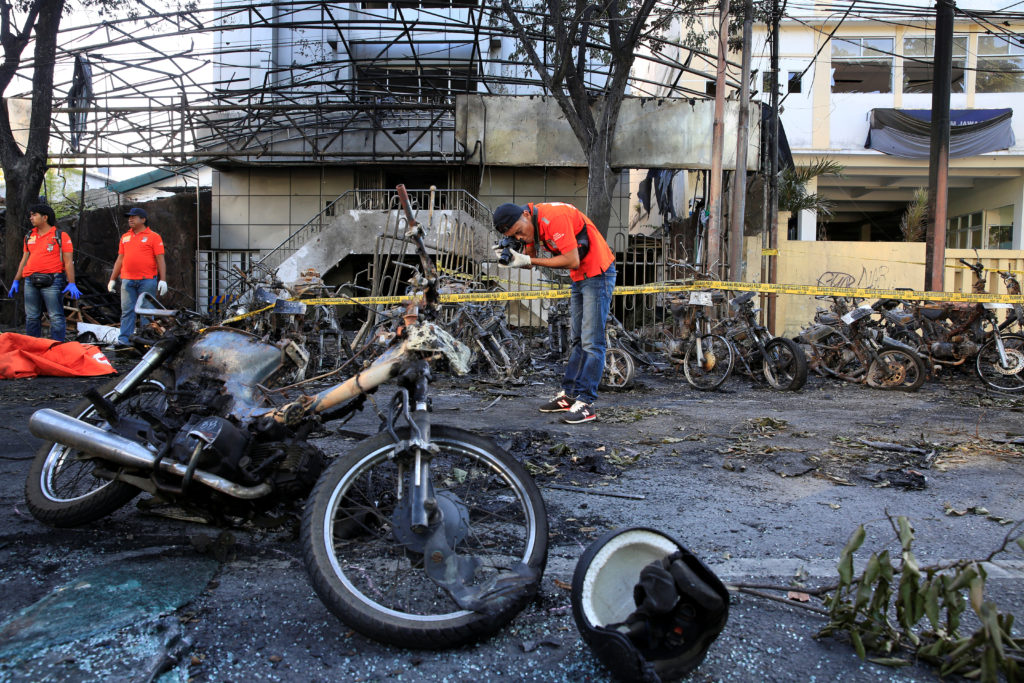 A forensic police officer takes pictures of debris near burned motorcycles following a blast at the Pentecost Church Central Surabaya (GPPS), in Surabaya, Indonesia May 13, 2018. REUTERS/Beawiharta - RC1B676437B0