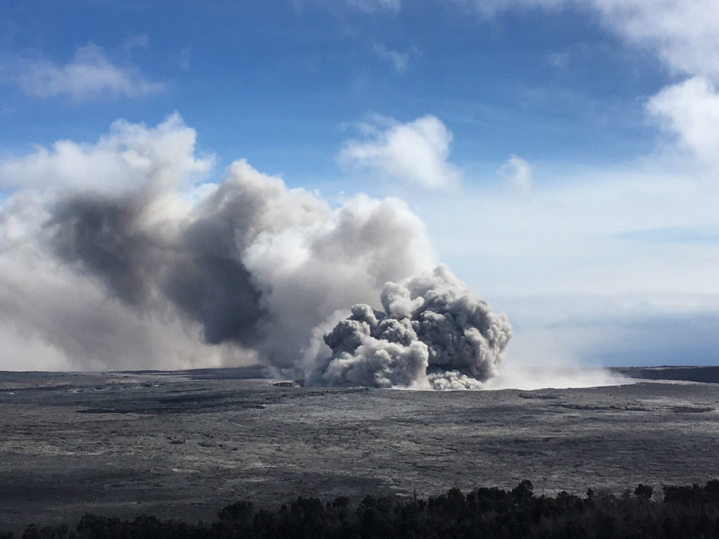 A pulse of ash rises from Halema'uma'u as part of semi-continuous emissions at Kīlauea's summit on May 23. Ash can be seen falling from the plume as it is blown downwind. Photo and caption by U.S. Geological Survey