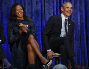 Former U.S. President Barack Obama sits with former first lady Michelle Obama prior during the unveiling of their portraits at the Smithsonian's National Portrait Gallery in Washington, U.S., February 12, 2018. REUTERS/Jim Bourg