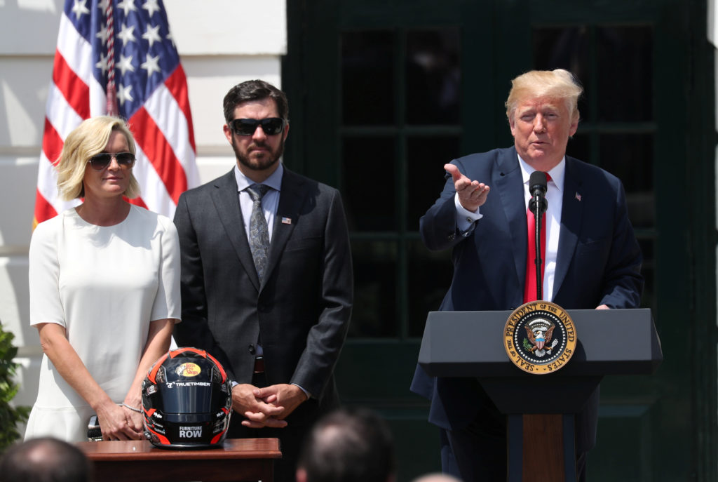 U.S. President Donald Trump speaks as NASCAR Cup Series champion Martin Truex Jr. and his partner Sherry Pollex look on during an event celebrating Truex and his winning team at the White House in Washington, U.S., , May 21, 2018. REUTERS/Kevin Lamarque