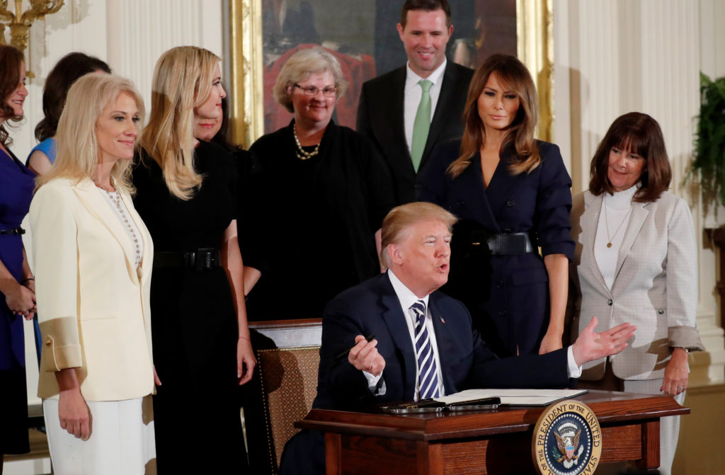 U.S. President Donald Trump signs an executive order related to military spouse unemployment during a celebration of military mothers and spouses at the White House in Washington, U.S., May 9, 2018. REUTERS/Leah Millis - RC144A006D00