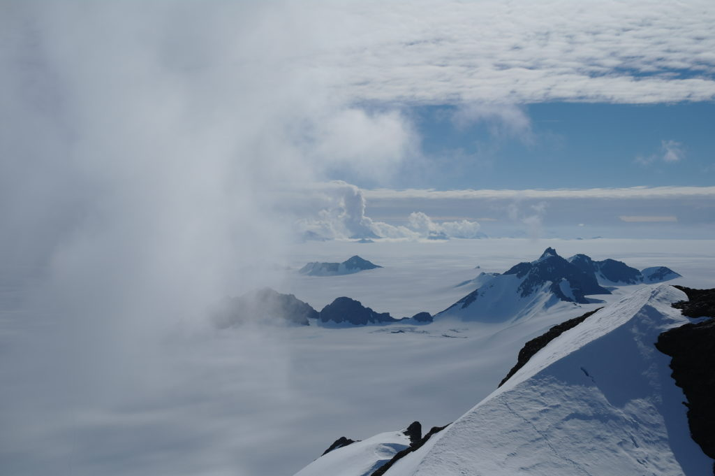 Summer clouds swirl in around the Staccato Peaks of Alexander Island, Antarctic Peninsula. High snowfall and strong weather gradients in this mountainous area make assessment of glacier mass balance particularly challenging. Photo by Hamish Pritchard, BAS