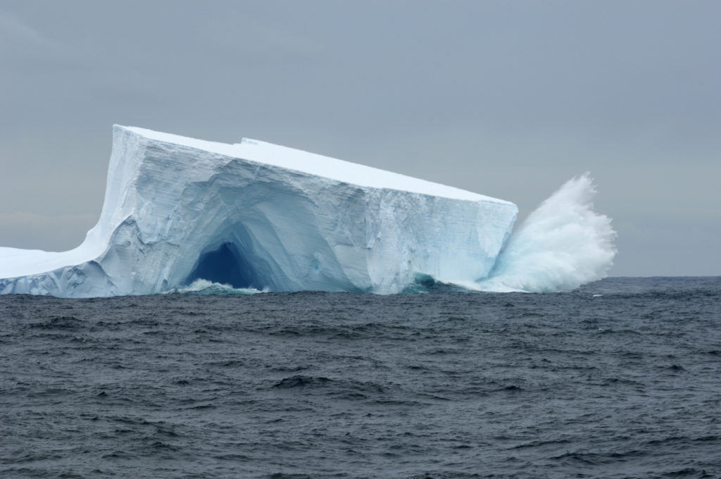 Antarctica, Scotia Sea, Near South Georgia, Waves Crashing On Tabular Iceberg With Cave. Photo by Wolfgang Kaehler/LightRocket via Getty Images