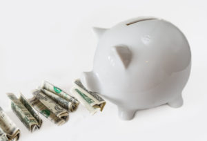 TORONTO, ONTARIO, CANADA - 2015/04/05: White piggy bank eating USA dollars one at a time, financial concept, saving one dollar at a time. Image over white background not isolated. (Photo by Roberto Machado Noa/LightRocket via Getty Images)