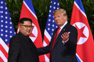 US President Donald Trump (R) gestures as he meets with North Korea's leader Kim Jong Un (L) at the start of their historic US-North Korea summit, at the Capella Hotel on Sentosa island in Singapore on June 12, 2018. - Donald Trump and Kim Jong Un have become on June 12 the first sitting US and North Korean leaders to meet, shake hands and negotiate to end a decades-old nuclear stand-off. (Photo by SAUL LOEB / AFP/Getty Images)